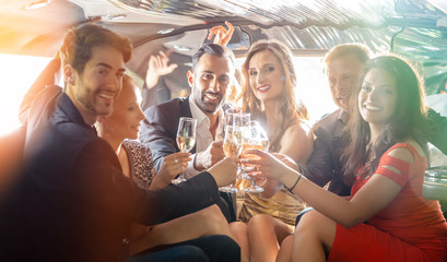 Group of women and men clinking glasses in a limousine