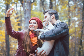 Woman and man with their dog on autumn walk taking a phone selfie
