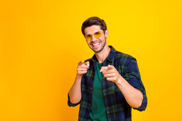 I pick you. Photo of funny guy indicating fingers on chosen candidate wear casual plaid shirt and sun specs isolated yellow color background