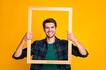 Photo of funny guy holding wooden picture frame looking through it posing wear casual checkered shirt isolated yellow color background