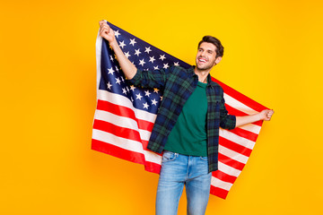 Photo of cool guy holding usa flag in hands exchange program student wear casual plaid shirt and jeans isolated yellow color background