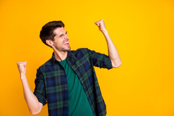 Photo of cool guy worried about football game raising fists supporting team wear casual plaid shirt isolated yellow color background