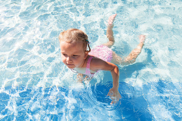 Little girl swimming in the pool on summer holidays