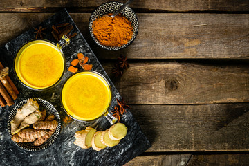Turmeric golden milk and ingredients on wood background, copy space