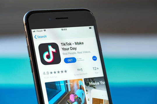 Kyiv, Ukraine - September 17, 2019: Studio shot of Apple iPhone 8 smartphone with TikTok mobile application on the screen, from the download page on App Store platform.