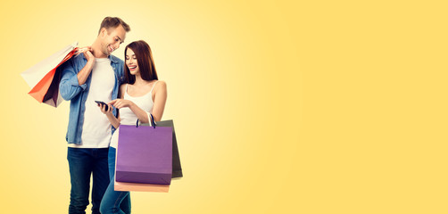 Photo of happy smiling lovely couple with smartphone and shopping bags, over yellow color background