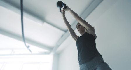 Fit muscular woman exercising with a kettlebell