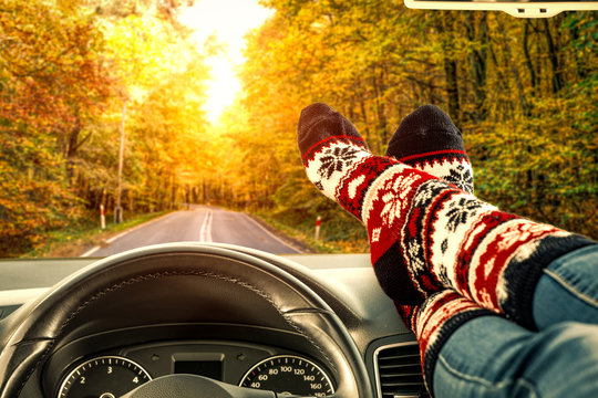 Woman legs with autumn socks in car interior and fall road background