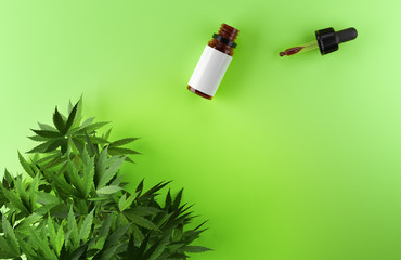 Cannabis leaves and CBD oil bottle on green background.