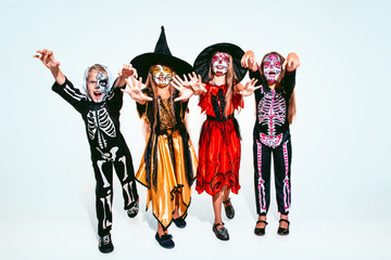 Kids or teens like witches and vampires with bones and glitter on white background. Caucasian...