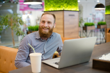 happy smiling young bearded caucasian cute man in shirt sitting in cafe with laptop and paper coffee cup during work break