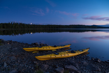 Fotomurales - Two kayaks on the shore of a lake during a tranquil evening. Jamtland, Sweden.
