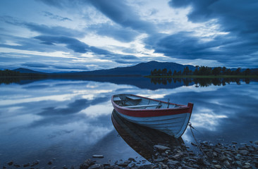 Old rowing boat at the rocky shore of a lake on a cloudy evening. Jamtland, Sweden.