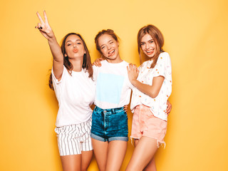 Three young beautiful smiling hipster girls in trendy summer clothes. Sexy carefree women posing near yellow wall in studio. Positive models going crazy and having fun.They show tongue