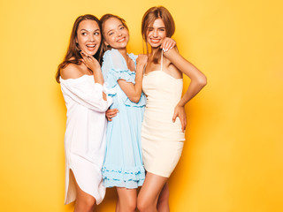 Three young beautiful smiling hipster girls in trendy summer clothes. Sexy carefree women posing near yellow wall in studio. Positive models going crazy and having fun Wall mural