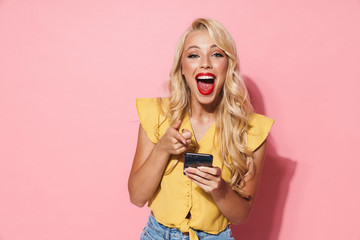 Image of beautiful woman laughing and holding cellphone