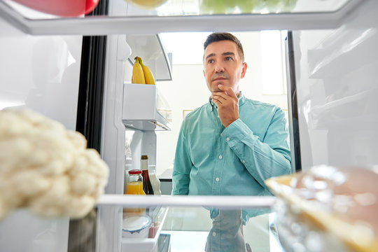 eating and diet concept - smiling middle-aged man man looking for food in fridge at kitchen