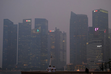 People look at the central business district skyline at dusk during haze in Singapore