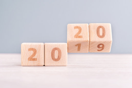 Abstract 2020 & 2019 New year countdown design concept - wood blocks cubes on wooden table and low saturation blue background, close up, copy space.