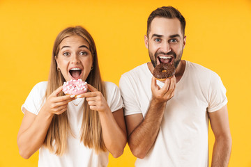 Image of pleased couple smiling while eating sweet donuts together