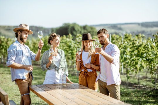 Group of young friends dressed casually having fun together, tasting wine on the vineyard on a sunny summer morning