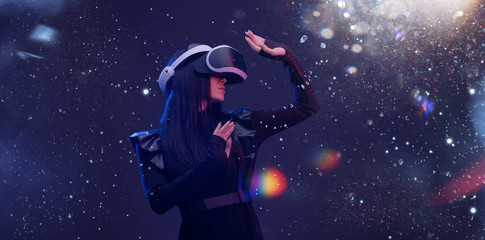 Wall Mural - Beautiful woman with flowing hair in futuristic dress over dark magic light background. Girl in glasses of virtual reality. Augmented reality, game, future technology concept. VR.