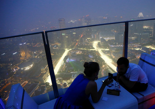 A couple dines as the Singapore F1 Grand Prix night race Marina Bay street circuit is seen shrouded by haze in Singapore