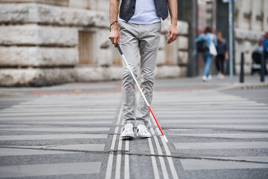 Midsection of young blind man with white cane walking across the street in city.