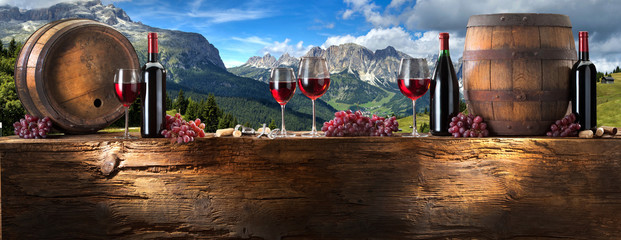 Spoed Foto op Canvas Alcohol red wine on an old wood with a landscape background