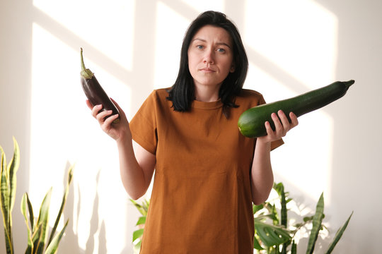 The girl in a T-shirt does not know what to choose - eggplant or zucchini. Hard choice.