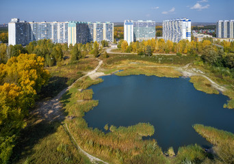 Bird's-eye aerial view on autumn park wit pond and on town with modern residential buildings. Novosibirsk, Siberia, Russia.