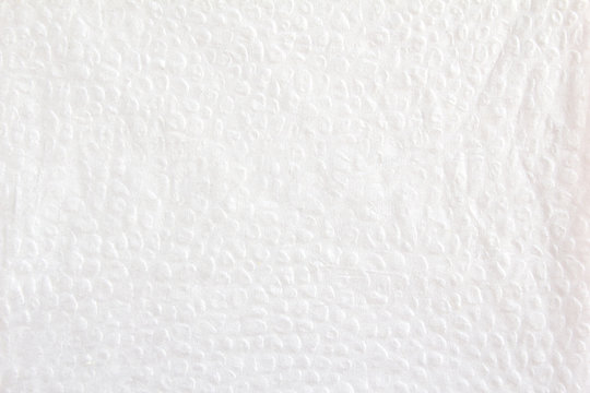 White crumpled paper napkin with pimpled surface texture background.