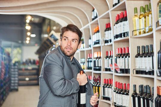 Mann steckt eine Flasche Wein in seine Jacke
