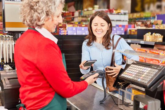 Kundin bezahlt kontaktlos mit NFC Smartphone