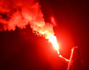 Red smoke bomb in a girl's hand at night