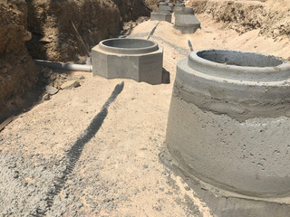 Storm water drainage reinforced concrete wells in the dug trench. Water drainage system under construction