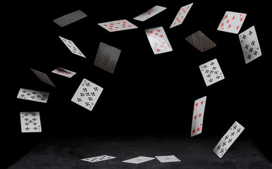 playing cards fall on a black table