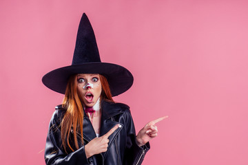 amazed and surprised redhaired ginger woman witch black hat and in leather jacket screaming and scaring with crazy make up on her pretty face in studio pink background copy spase Wall mural