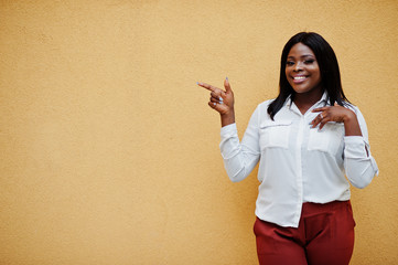 Formally dressed african american business woman in white blouse and red trousers isolated on yellow background and show finger to free space. Successful dark skinned businesswoman.