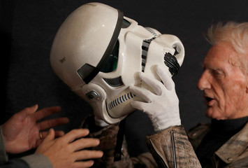 """Syd Wragg, who wore this Stormtrooper helmet in the film """"Star Wars: A New Hope"""", tries on the helmet again at a preview of a film and tv memorabilia sale in London"""