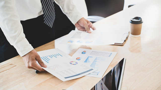 Businessman compare finance data on table.