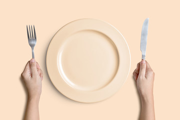 Yellow plate with silver fork and knife on pink background with clipping path.