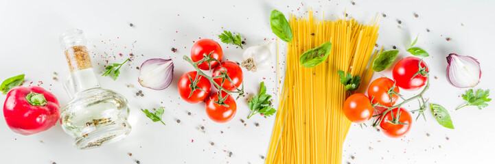 Traditional ingredients food  spaghetti pasta. Mediterranean italian dinner concept background. Dried pasta, garlic, olive oil, basil, tomatoes. White stone background. Top view with copy space.