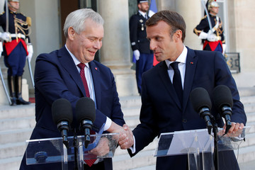 French President Emmanuel Macron shakes hands with Finland's Prime Minister Antti Rinne after a joint statement at the Elysee Palace in Paris