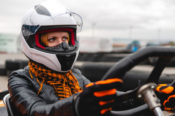 Portrait of a pretty girl wearing a white helmet close up, detail of Go-kart. karting track racing, copy space. serious look, determination, active lifestyle, extreme sport