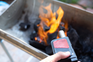 Close up of man's hand holding and using air fire blower to set stove charcoal fire.