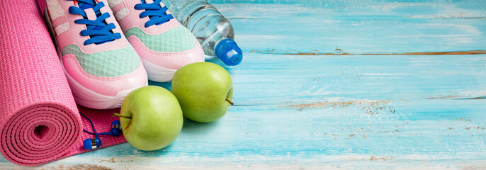 Pink yoga mat, sport shoes, bottle of water and apples on blue wooden background. Sport, healthy lifestyle, yoga concept. Female sport equipment. Copy space