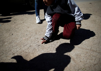 A child plays with marbles in Claypole, on the outskirts of Buenos Aires