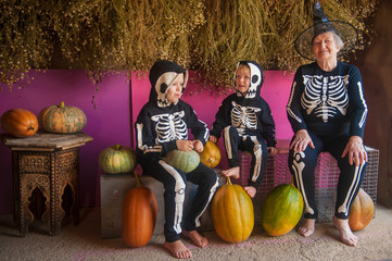 elderly witch grandmother is sitting in barn with her grandchildren. Children and old woman are dressed in skeleton costumes. Halloween eve with pumpkins in hands