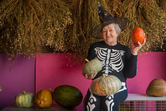 An elderly witch grandmother is sitting in a barn. old woman dressed in skelton costumes. Halloween eve with pumpkins in hands